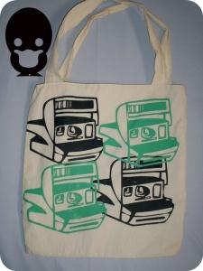 Bolsa em algodão cru, estampada apenas na frente, forro e bolso interno e dois botões de pressão p/ o seu fechamento. R$ 40,00 + frete.